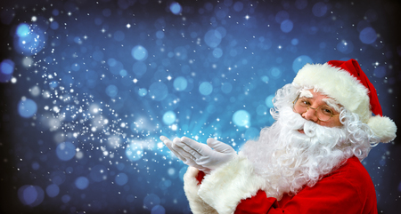 Santa Claus with magic light in his hands. Happy Santa Claus blowing   Magic Christmas stars