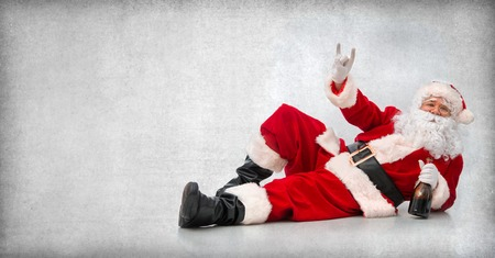 Drunk and happy Santa Claus lying on the floor with a bottle of wine and makes a hand sign Stockfoto