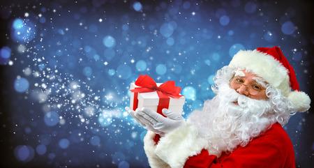 Père Noël avec une lumière magique dans ses mains. Joyeux Père Noël soufflant des étoiles de Noël magiques