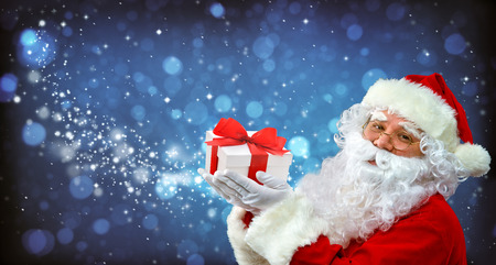 Santa Claus with magic light in his hands. Happy Santa Claus blowing  Magic Christmas stars Stock Photo
