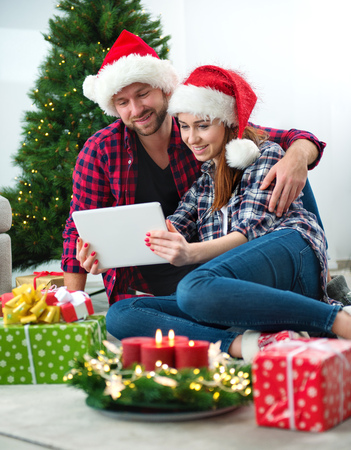 Young couple with Santa Claus hats shopping online Christmas gifts on a tablet Stock Photo