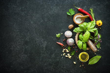 Herbs and spices on black stone table. Ingredients for cooking. Top view with copy space Stock Photo
