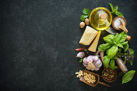 Ingredients for homemade green basil pesto on black stone table. Parmesan cheese, basil leaves, pine nuts, olive oil, garlic, salt and pepper Archivio Fotografico