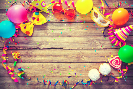 Colorful birthday or carnival frame with party items on wooden background Stock Photo