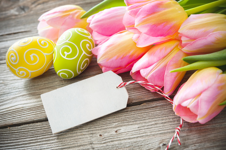 Colorful Easter eggs and tulips  with an empty tag on wooden background Stock Photo