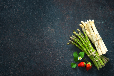 Fresh green and white asparagus with strawberries on dark background