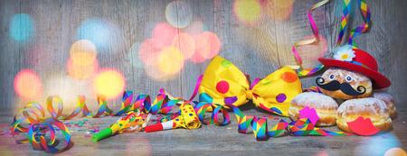 カーニバルの粉砂糖は、紙のストリーマーとパーティーの蝶ネクタイでドーナツを上げました