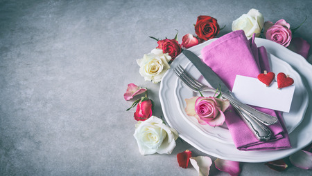 Valentines day table setting with plate, roses, red ribbon and hearts. Holidays background. Valentines day background Stock Photo