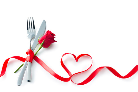 Silverware tied up with red ribbon in heart shape isolated on white background. Concept Valentines Day dinner. Restaurant party celebration Archivio Fotografico