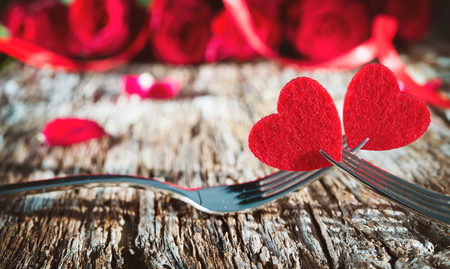 Hearts on forks in front of red roses. Concept Valentines Day dinner