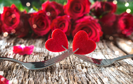 Hearts on forks in front of red roses. Concept Valentine's Day dinner Stok Fotoğraf