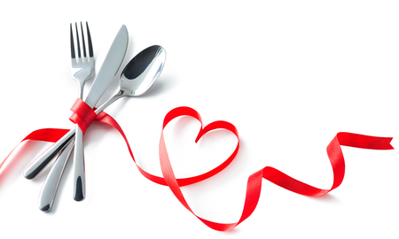 Silverware tied up with red ribbon in heart shape isolated on white background. Concept Valentines Day dinner. Restaurant party celebration Stock Photo