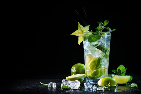 Mojito cocktail with fresh lime and mint on a black stone board 스톡 콘텐츠