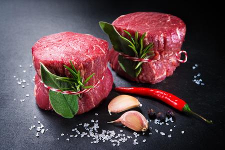 生の牛肉のフィレステーキミニョンと暗い背景にスパイス