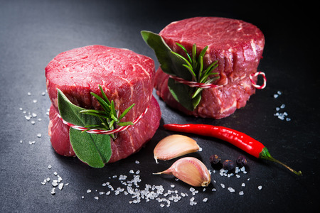 Raw beef fillet steaks mignon with spices on dark background