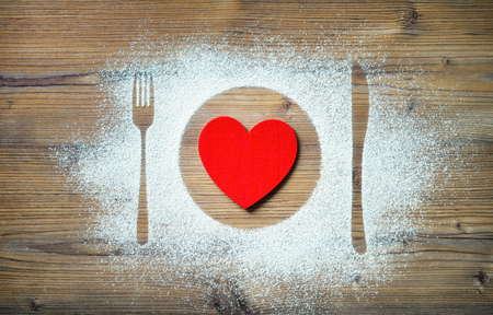 Fork, knife and plate with red heart, flour sprinkled around the wooden board