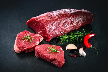 carne fresca y cruda . sin cocer pedazo de solomillo con filetes y especias listos para cocinar en el fondo oscuro