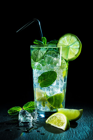 Mojito cocktail with fresh lime and mint on dark background