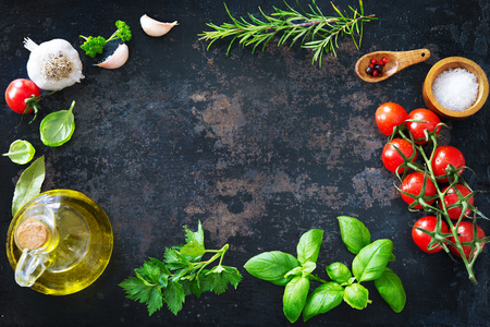 Mediterranean healthy cuisine. Olive oil, tomatoes, garlic, parsley, basil, spices on dark background Stock Photo