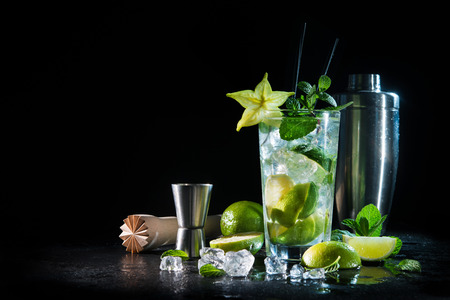 Mojito cocktail with fresh mint, lime, ice cubes and bar shaker on dark background