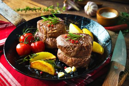 Beef steak. Juicy medium beef fillet steaks mignon in pan on table Фото со стока