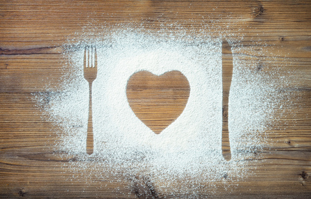 Fork, knife and plate in heart shape, flour sprinkled around the wooden board