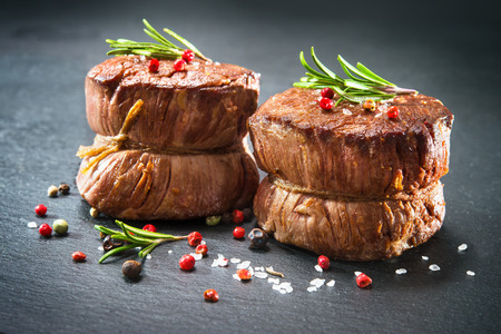 Grilled beef fillet steaks mignon with spices on dark background