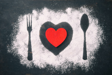 Spoon, fork and plate with red heart, flour sprinkled around the dark table Stock Photo