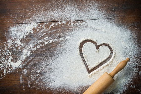 Baking background with the rolling pin, heart shape and flour on the wooden table. Copy space for text. Top view Foto de archivo - 96133653