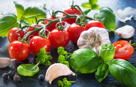 Ripe tomatoes with fresh basil, garlic and other herbs with water drops on slate plate. Mediterranean food healthy diet. Fresh vegetables spices and Italian herbs Stock Photo