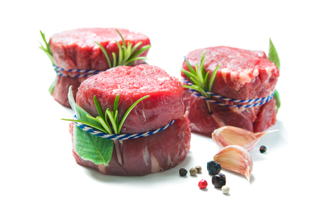 Raw beef fillet steaks mignon with spices isolated on white background