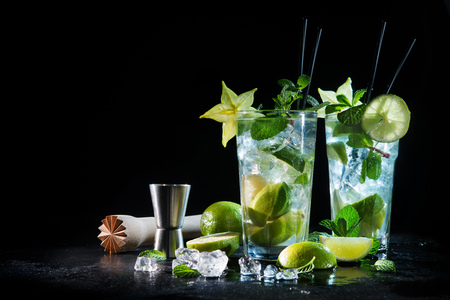 Two glasses of mojito cocktail with fresh lime and mint on a black stone board