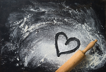Baking background with the rolling pin, heart shape and flour. On the dark table. Copy space for text. Top view