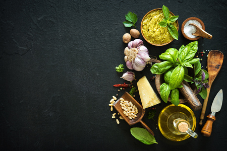 Ingredients for homemade green basil pesto on black stone table. Parmesan cheese, basil leaves, pine nuts, olive oil, garlic, salt and pepper Stockfoto