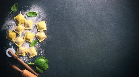 Ravioli with spinach and ricotta on dark background, top view