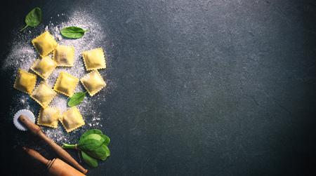 Ravioli con spinaci e ricotta su sfondo scuro, vista dall'alto