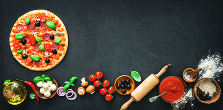 Delicious pizza with ingredients and spices. Top view with copy space on wooden table Stock Photo