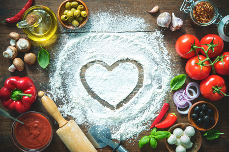 Ingredients and spices for making homemade pizza. Top view with copy space on wooden table
