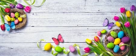 Easter background. Colorful spring tulips with butterflies and painted eggs on vintage wooden board