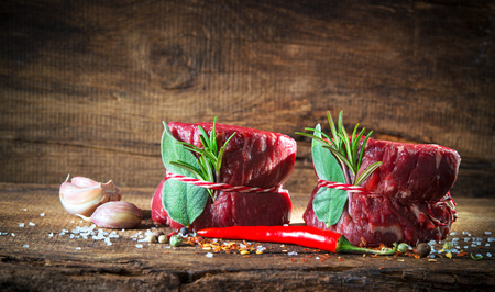 Raw beef fillet steaks mignon with spices on wooden background Stock Photo