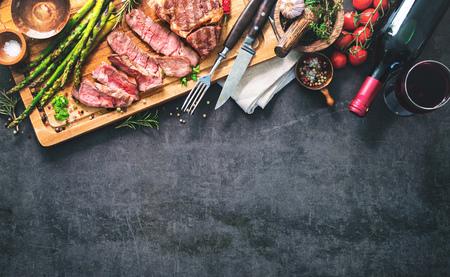 Roasted rib eye steak with green asparagus and wine on dark background