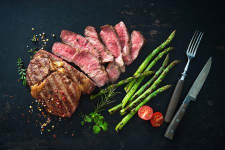 Roasted rib eye steak with green asparagus on dark background