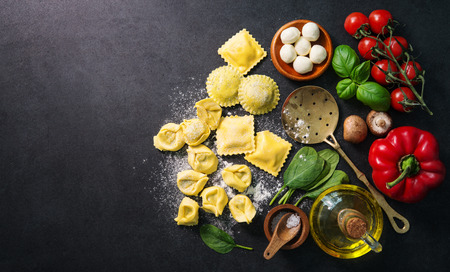 Homemade fresh Italian ravioli pasta on dark background, top view