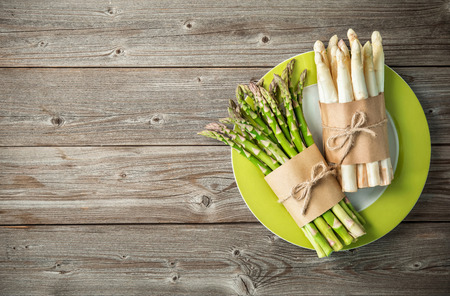 Bunches of fresh green and white asparagus on wooden background. Top view, copy space