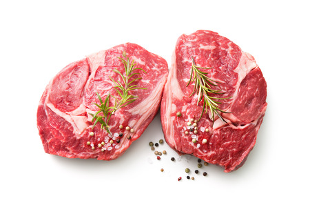 fresh raw rib eye steaks isolated on white background, top view