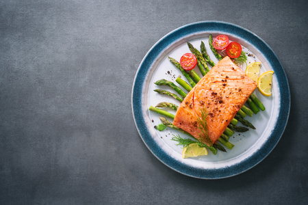 Grilled salmon garnished with green asparagus and tomatoes.Top view