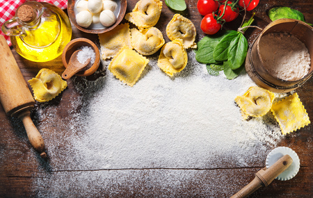 Top view on homemade pasta ravioli on old wooden table with flour, basil, tomatoes and vintage kitchen accessories