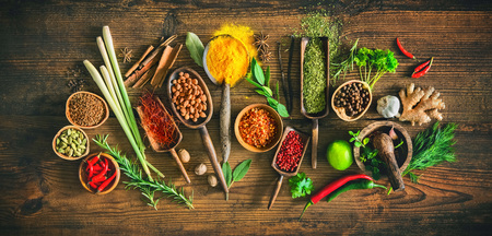 Colourful various herbs and spices for cooking on wooden board