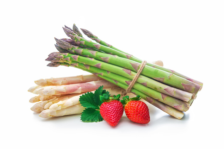 Green and white fresh asparagus with strawberries. Healthy vegetables isolated on white background Stock Photo