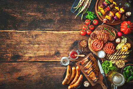 Grilled meat and vegetables on rustic wooden table. Barbecue menu